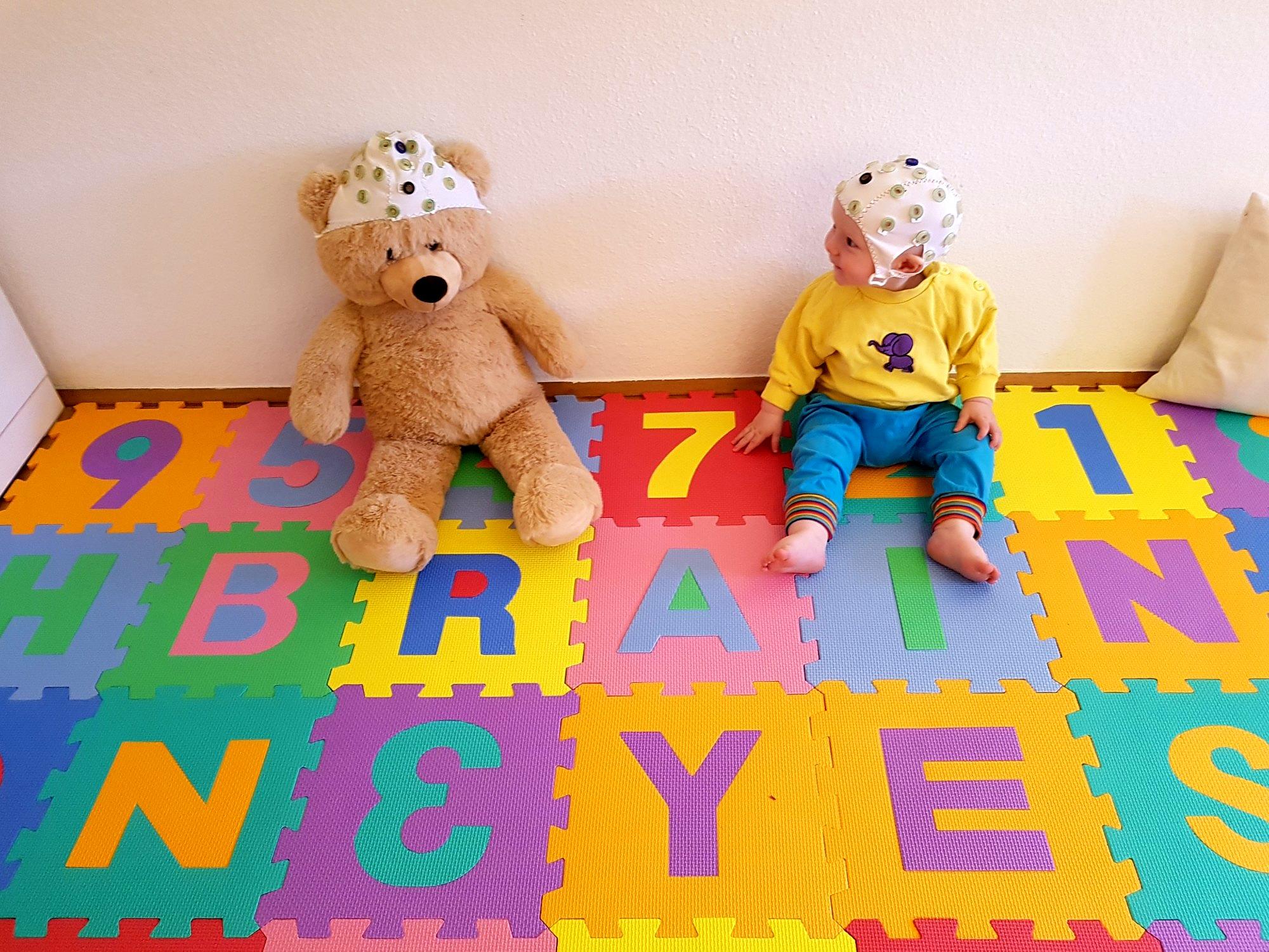 """Ein Baby mit EEG-Haube sitzt neben einem Tedyybären mit EEG-Haube auf einer Matte, auf der """"Brain"""" steht"""